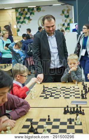 ST. PETERSBURG, RUSSIA - DECEMBER 29, 2018: Grandmaster Shakhriyar Mamedyarov, Azerbaijan watch children playing chess during World Blitz Chess Championship