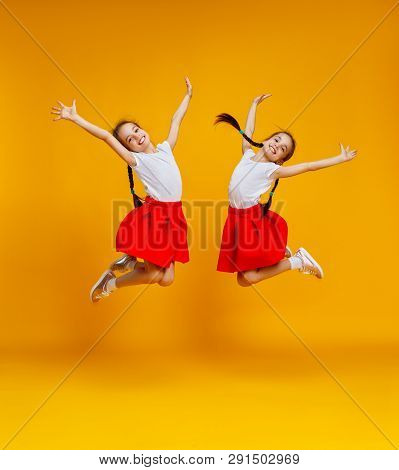 Funny Children Girls Twins Jumping On A Colored Yellow Background