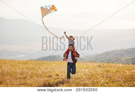 Happy Family Father And Child Daughter Launch A Kite On Meadow