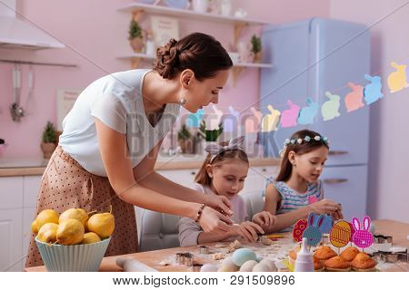 Charming Young Woman Helping Her Kids During Cooking