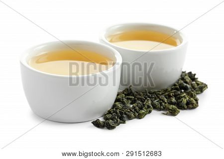 Cups Of Tie Guan Yin Oolong And Tea Leaves On White Background