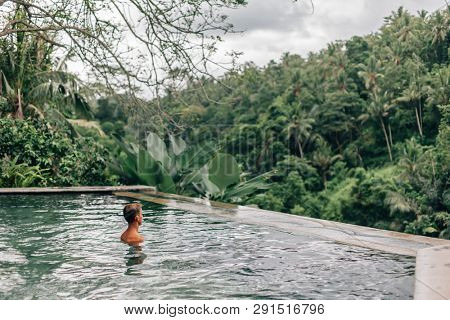Human relaxing in Bali infinity pool with jungle view