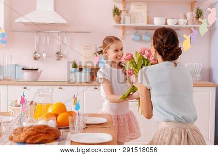 Positive Delighted Kid Presenting Flowers To Her Mom