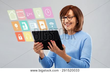 technology, automation and internet of things concept - smiling senior woman in glasses with tablet computer using smart home app over grey background