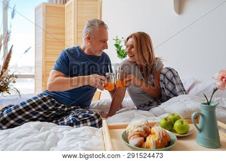 Couple Clanging Glasses With Juice Having Breakfast In Bed