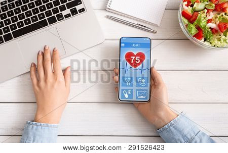 Mobile Phone Synchronizing Health Data With Computer, Woman Using Healthtrack Application And Laptop