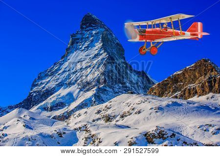 Child girl pilot aviator in airplane flying over winter mountains. The travel for ski by air concept.