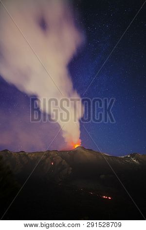 smoke from Etna Volcano during a eruption at night against starry sky, Sicily