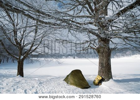 a tent and backpack by frozen lake in Nebrodi Park, Sicily