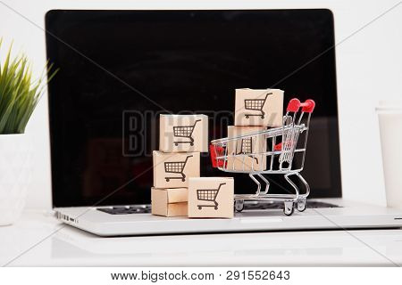 Online Shopping Ecommerce And Delivery Service Concept : Paper Cartons With A Shopping Cart Or Troll