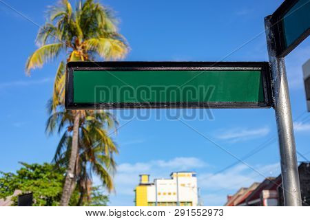 Blank Street Sign On Sunny Urban Landscape With Palm Trees And Yellow Building. Green Metallic Sign