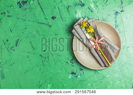 Empty Beige Plate And Cutlery With Daffodils On A Napkin. Top View, Green Concrete Surface Backgroun