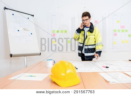 Smart young businessman talking on mobile phone while working on blueprint at office table
