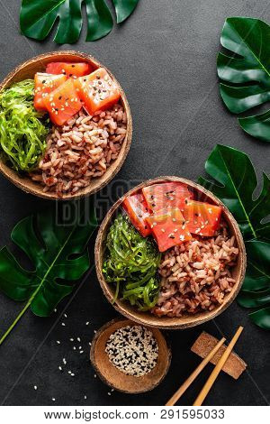Poke bowl with raw salmon fish, chuka salad and rice in coconut bowls on black background poster