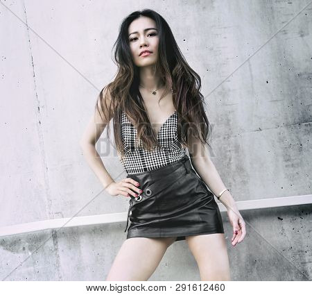 Beautiful young woman wearing leather skirt.