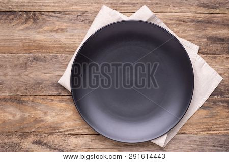 Black empty plate with kitchen towel on wooden background, top view