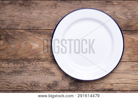White empty enamel plate on old wooden table, top view