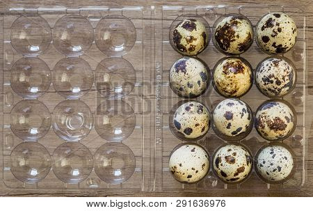 Top View Of Quail Eggs In Plastic Container On Brown Wooden Background.