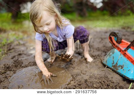 Funny Little Girl Playing In A Large Wet Mud Puddle On Sunny Summer Day. Child Getting Dirty While D