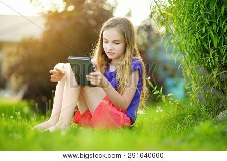 Cute Little Girl Sitting In A Garden And Reading An Ebook On Sunny Summer Evening. Education For Kid