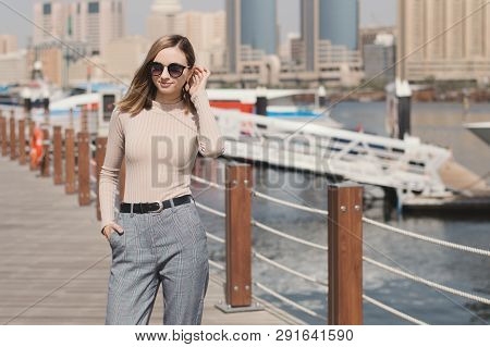 European Female In Classic Beige Turtleneck And Trousers Standing At Marina Promenade In A Sunny Day