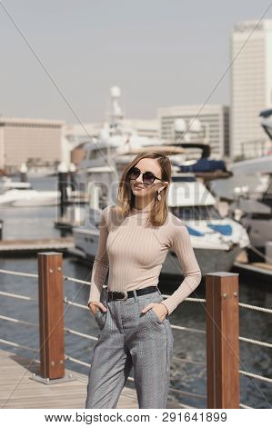 Young European Female Standing Near Yachts At Pier Or Marina Promenade In A Sunny Day
