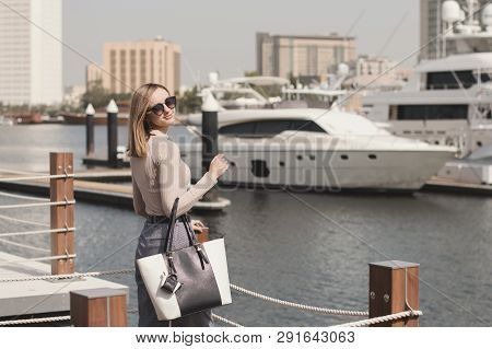 Young European Woman With Blond Long Bob Hair, Beige Sweater, Stylish Trousers And Big Bag Standing