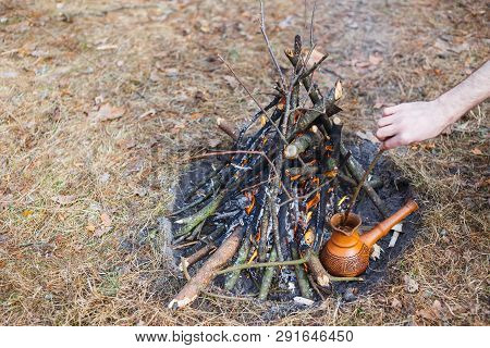 At The Stake In The Spring Forest, A Clay Turkish Coffee Pot Is Heated Against The Grass. In The Fra