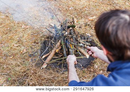Bonfire In The Spring Forest On The Background Of Withered Grass. In The Frame Head, Shoulder And Ar