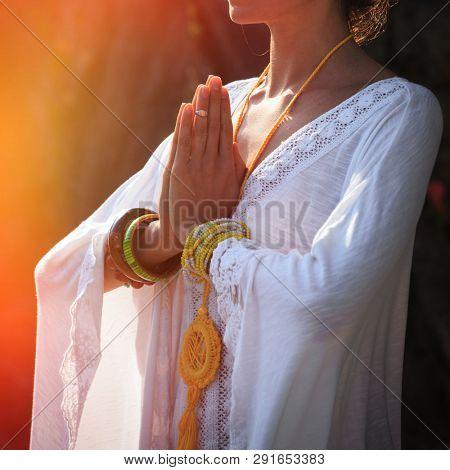 woman hands in mudra namaste gesture practice yoga outdoor day shot close up