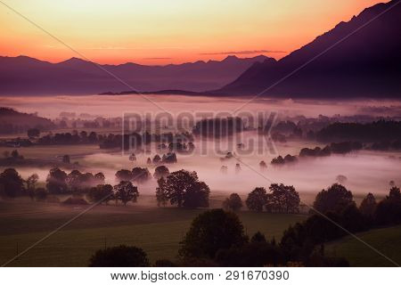 Breathtaking Morning Lansdcape Of Small Bavarian Village Covered In Fog. Scenic View Of Bavarian Alp