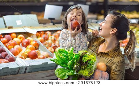 Family In The Supermarket. Beautiful Young Mom And Her Little Daughter Smiling And Buying Food.