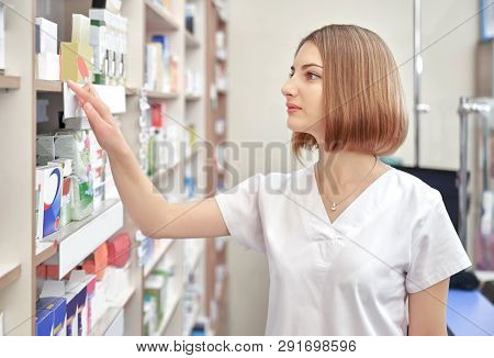 Professional Pharmacist Checking Medicaments, Working In Drugstore. Beautiful Woman Wearing In White