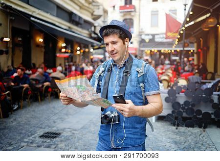 Backpacker Traveler Man Traveling Alone On Crowded Streets In Old Town. Neck Camera And Holding City