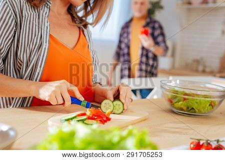 Woman Wearing Striped Blouse Cutting Vegetables For Salad