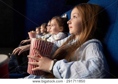 Pretty, Little Girl Holding Popcorn Bucket, Sitting With Friends In Cinema, In Comfortable Chairs. C