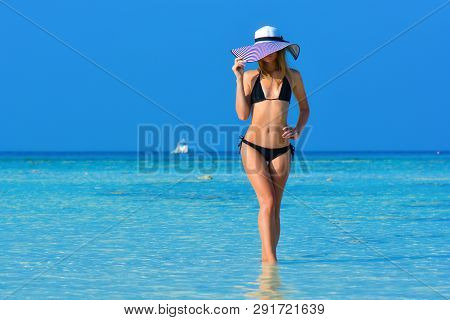 Fit Girl On A Tropical Beach With Hat. Sexy Black Bikini Body Woman On Paradise Tropical Beach. Beau