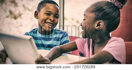 Smiling children using digital tablet in classroom at school