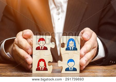 Businessman Collects Puzzles Symbolizing The Team Of Employees. Combining Teams And People To Perfor