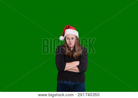 Sulking Young Women Frowning Crossed Arms Wearing A Red And White Santa Claus Christmas Hat On Green