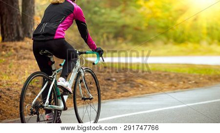 Young Woman in Bright Pink Jacket Riding Road Bicycle in the Park in the Warm Spring Morning. Healthy Lifestyle Concept.