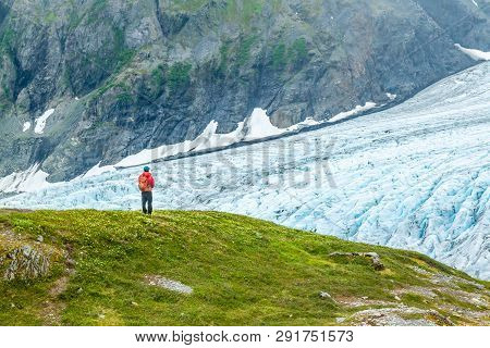 A Man In A Red Jacket Is Gazing Out Over Exit Glacier In Alaska, Usa. Man Is Standing On Green Grass