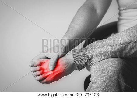 Causian Man Holds Hands To His Painful Feet, Pain In Foot.  Black And White Photography. Red Color I