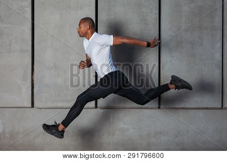 Black Athlete Running Against Concrete Wall. Training Outdoor