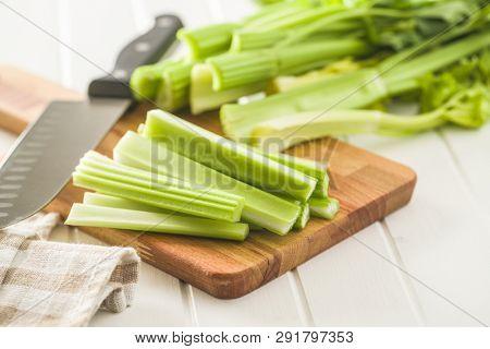 Celery sticks. Cutting celery stalks on cutting board.