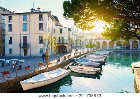 Desenzano del Garda, Italy. Calm beautiful view of italian lake Garda. Amazing landscape of ancient city, sky and mountains. Panorama of gorgeous Lake Garda, buildings and boats. Heaven on Earth.