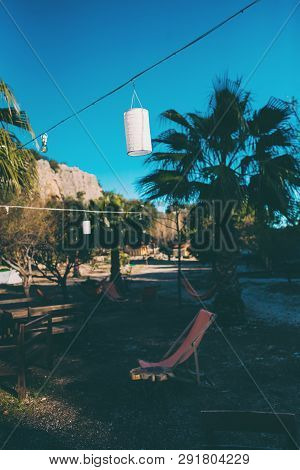 Recreation area in a climbing campsite. Hammock and chaise lounge against mountains and blue sky. Table and chairs on green grass. Resting place in nature. Lighting open area. Holidays in Turkey. poster