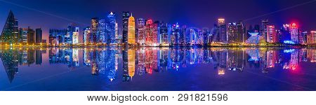 Banner Of Capital City Of Qatar By Night. Doha West Bay Skyline Mirroring In Doha Bay. Panorama Of G