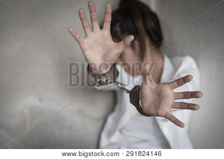 Woman's Hands In Handcuffs. Women Violence And Abused Concept. Human Trafficking.  Stop Violence Aga