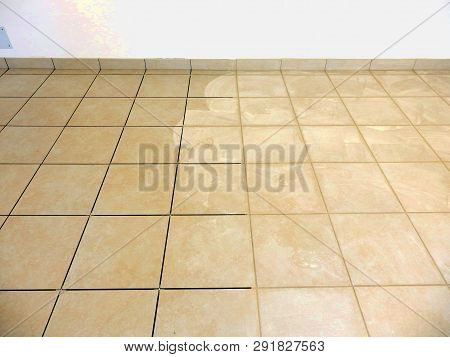 Newly Laid Beige Floor Tiles And Plinths With Beige Grouting Being Applied